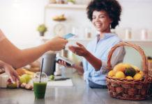 Une jeune femme paye son smoothie avec sa carte Pass restaurant 2e generation
