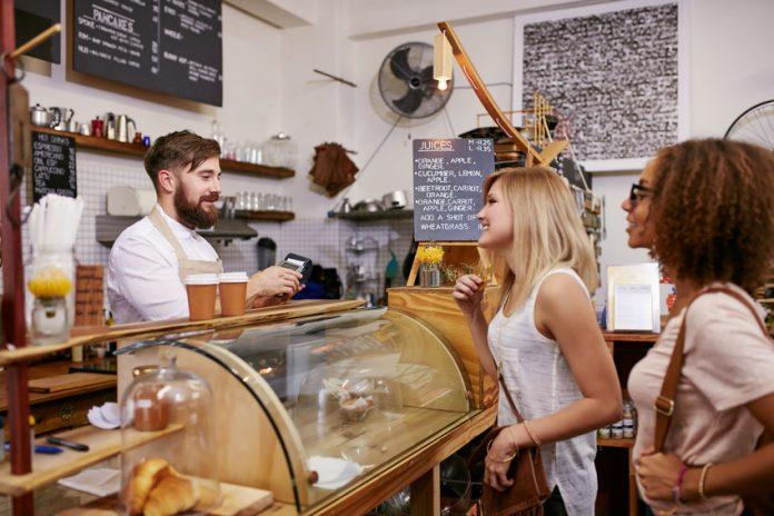 Une jeune femme fait un paiement dans une boulangerie par carte Pass Restaurant 2e génération